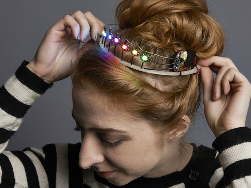 A young women placing a light up tiara on her head